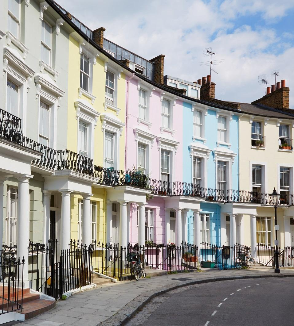 Colourful West End London houses in Primrose hill lined up. They are painted grey, yellow, pink, blue and beige.