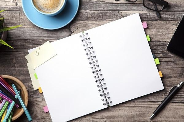 A notebook on a desk with a cup of coffee and a container of pens.