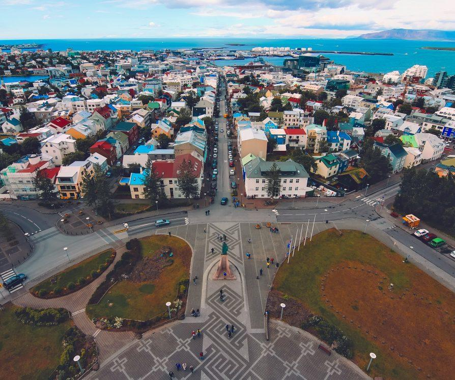 An overhead shot of Iceland's city centre, near the coast with the sea in the background and colourful houses.