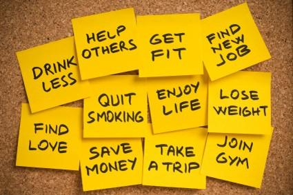 Eleven yellow post-it notes with a cork board with common New Year's resolutions.