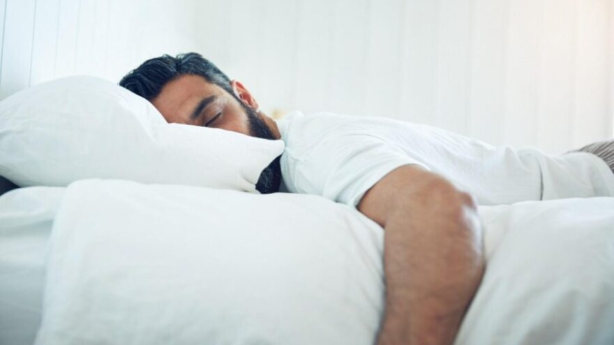 A man with dark hair and a beard in pyjamas sleeping on a white bed, bedsheet, duvet and pillow.
