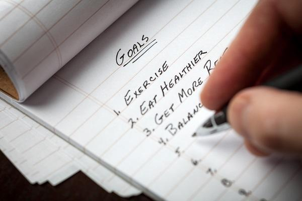 A person writes a list of goals including exercise, eating healthier, getting more rest and staying productive at work.