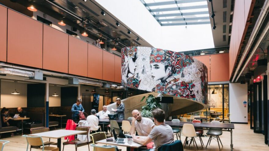 An interior shot of a WeWork building, with colour artwork, one of the best coworking spaces in the UK.