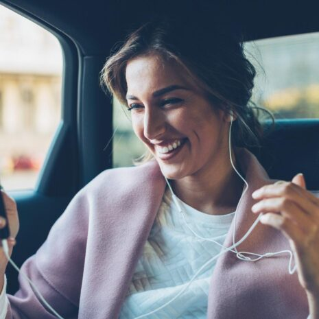 Young woman with smart phone and headphones on the back seat of a car.