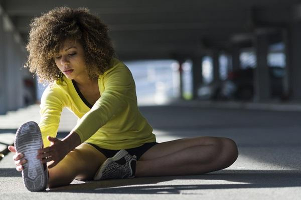A desk assistant in her workout gear stretching in the carpark of her workplace before going for a run.