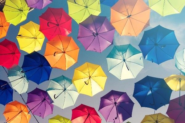A shot of several colourful umbrellas in the sky, symbolising diversity hiring.