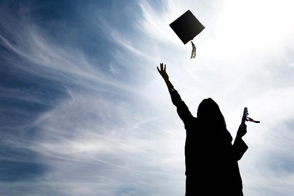 A shadow of a graduate in a cap and gown, throwing her hat into the air on a sunny day.