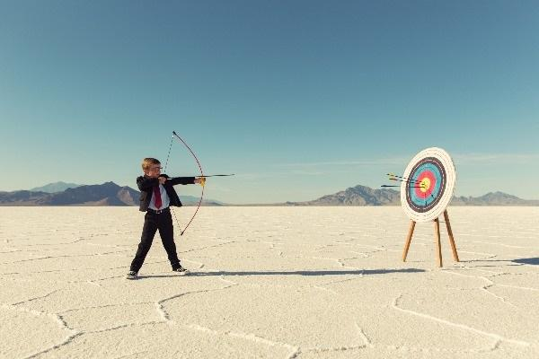 A little boy using a bow and arrow to shoot a target in the middle of a hot and sunny desert.