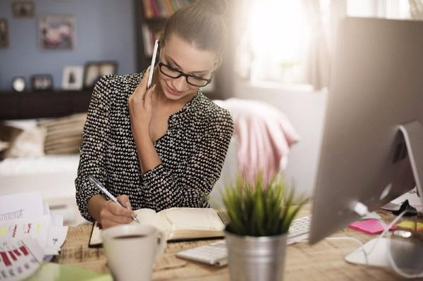 A private PA on the phone in her home office while at her desk and writing in her notebook.