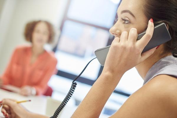 A career receptionist picking up the phone at her office with her colleague in the background.