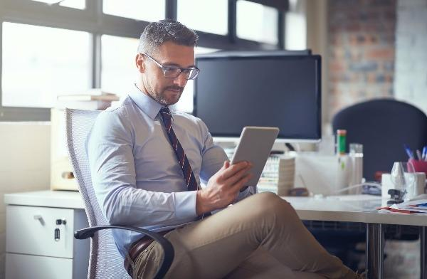 A smart business man sits at his desk with an iPad.