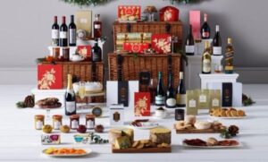 A luxury Christmas hamper with wine bottles, boxes, cheese, salami, cookies, pinecones, red ribbons, quince paste and jam.