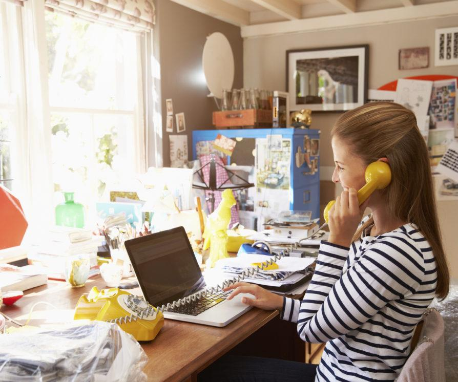 Woman on laptop running her business while working from home, with a yellow landline phone and a cluttered desk.