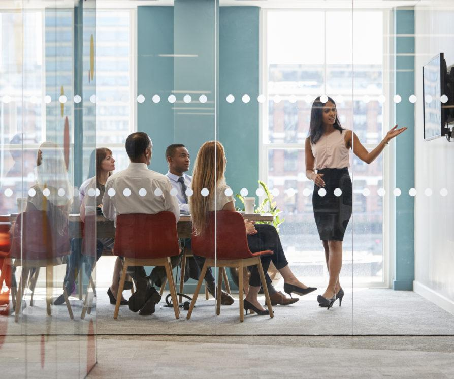Female boss shows a presentation on screen at a business meeting to onboarded graduates in an office with glass walls.
