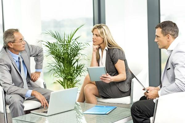 Three business people sitting in a recruitment agency office using wireless technology and discussing core hiring decisions.