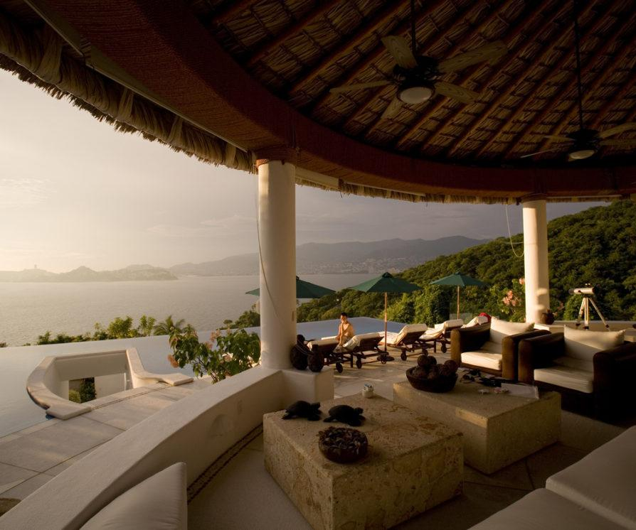 An open air villa with an infinity pool and a view looking out to the ocean during sunset in Acapulco Mexico.