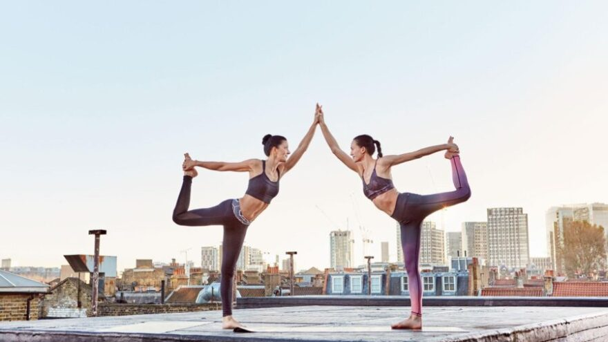 Two young women practicing a yoga pose together, partaking in a yoga class on a rooftop in the middle of London.