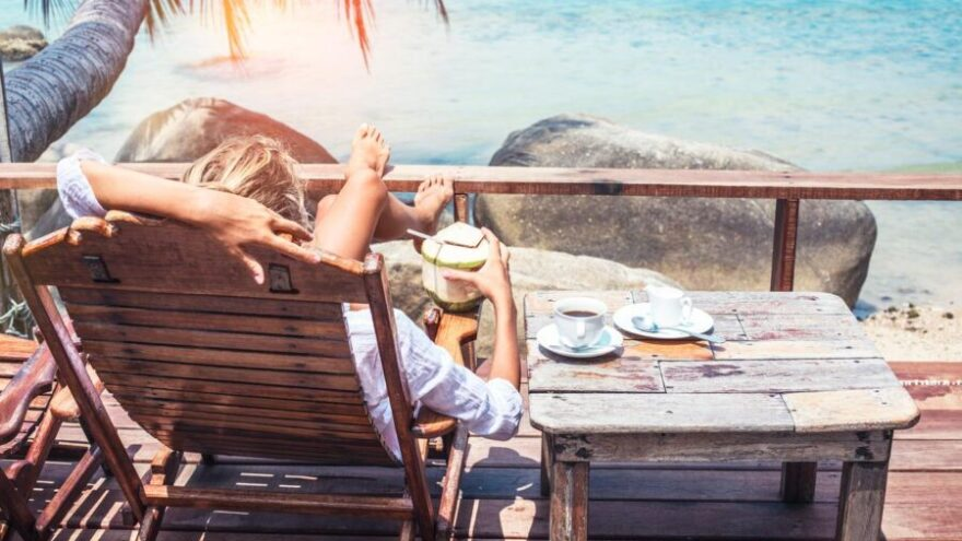 A woman laying on a deckchair on a tropical island, one of Brown + Hudson's insider travel tips for private PAs.