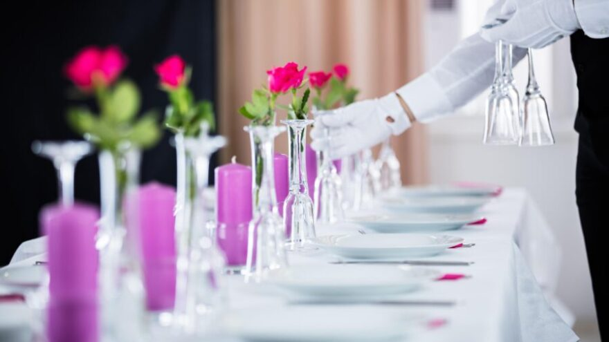 A butler places water glasses on a white tablecloth in a mansion, which is one of the qualities every butler should possess.