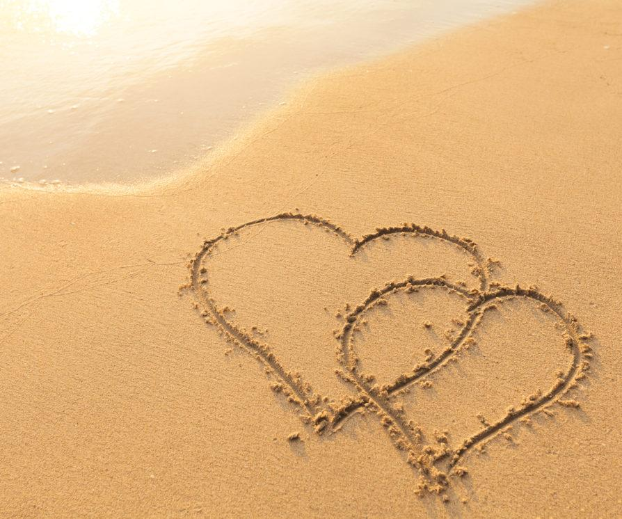Two hearts drawn out of the sand on Love Island, representing the reality TV show.