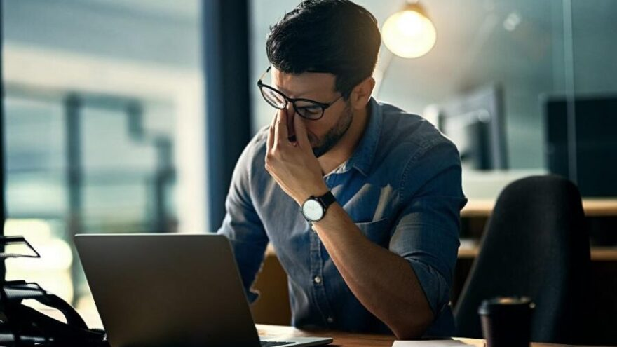 A man in smart business clothes sitting in an office rubbing his nose and closing his eyes while suffering from burnout.