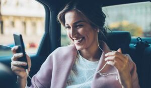 A private PA looking at her phone and smiling in a car while she's driven to the house of her principal.