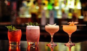 A line of cocktails, red, pink, orange and yellow, sitting on a bar with bottles of liquor blurred out behind.
