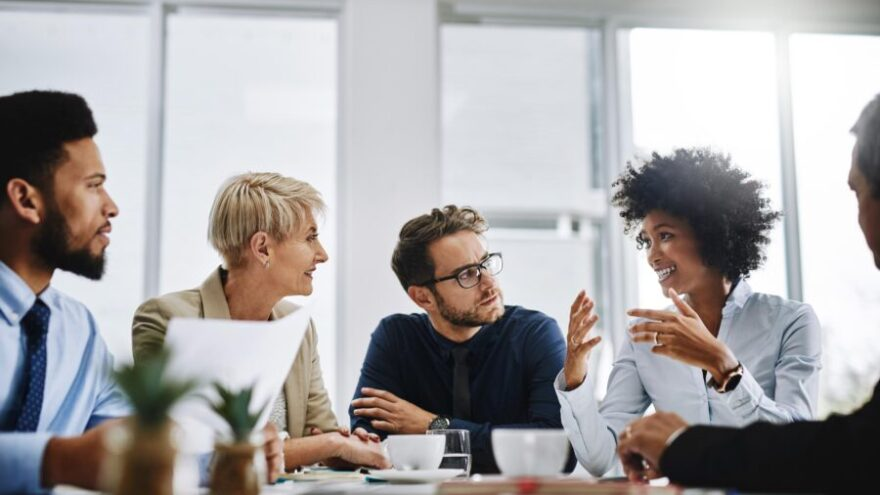 A group of managers sitting around a desk, discussing how employee engagement is shifting in 2019.