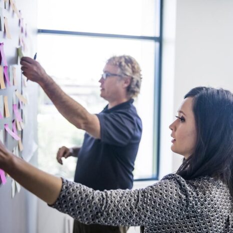 An office manager working with her colleague to put post it notes on a wall to organise their brainstorming session.