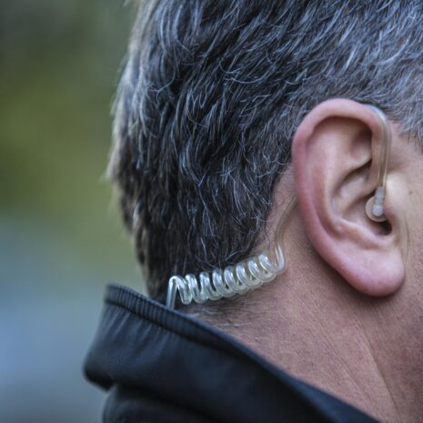 A close up on a close protection officer's earpiece while he's working a job outside, protecting the principal who hired him.
