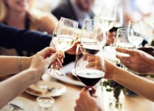 Business people celebrate a Christmas party together by cheersing with their wine glasses - a unique and bespoke gift.