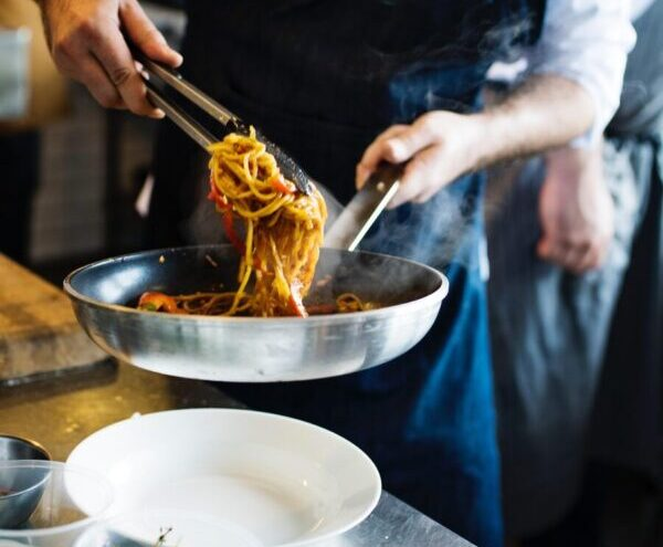 chef cooking pasta in pan