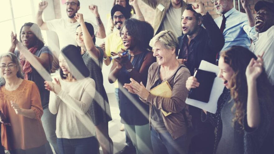 Group of people smiling and clapping at work