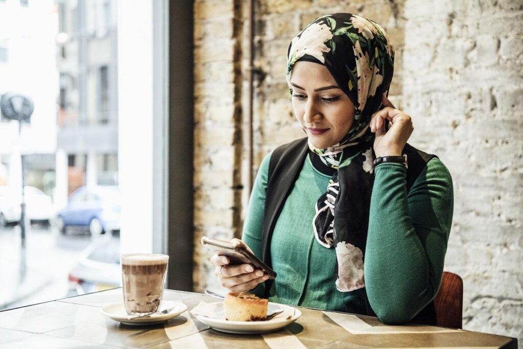 Woman in hijab texting on phone, hot drink and snack on table, leaning on elbow