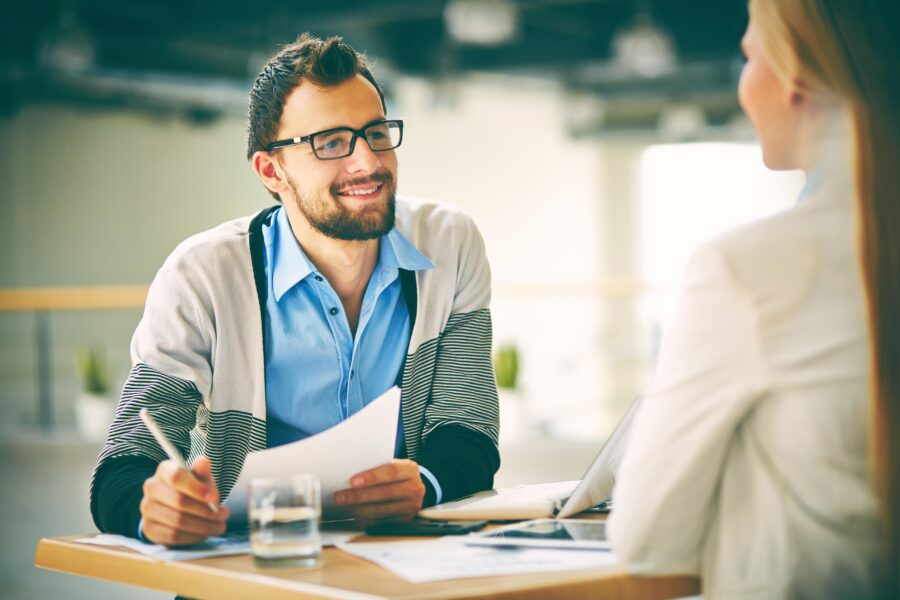 Smiling businessman with paper listening to his colleague at meeting