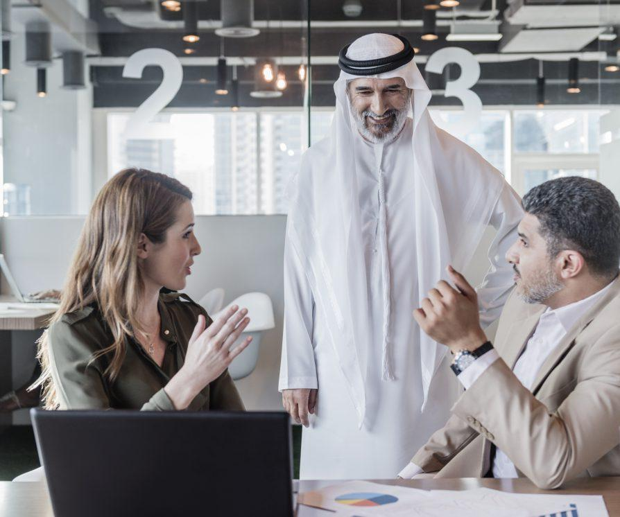 A group of three human resources professionals discussing business strategy and decisions in modern office in the Middle East.