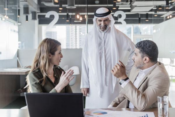 Business people discussing global business in modern office, mature Arab businessman wearing traditional clothing