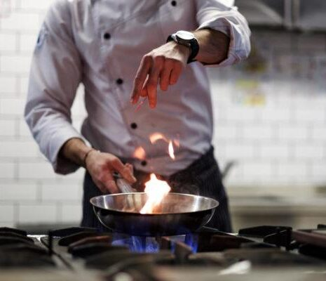 A chef cooks in a kitchen. He gently fries the vegetables while cooking the dish.