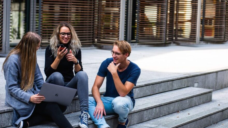 Three creative workers sit on the steps outside with a laptop