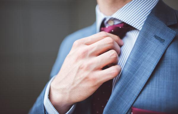 Closeup of a stylish businessman fixing his tie