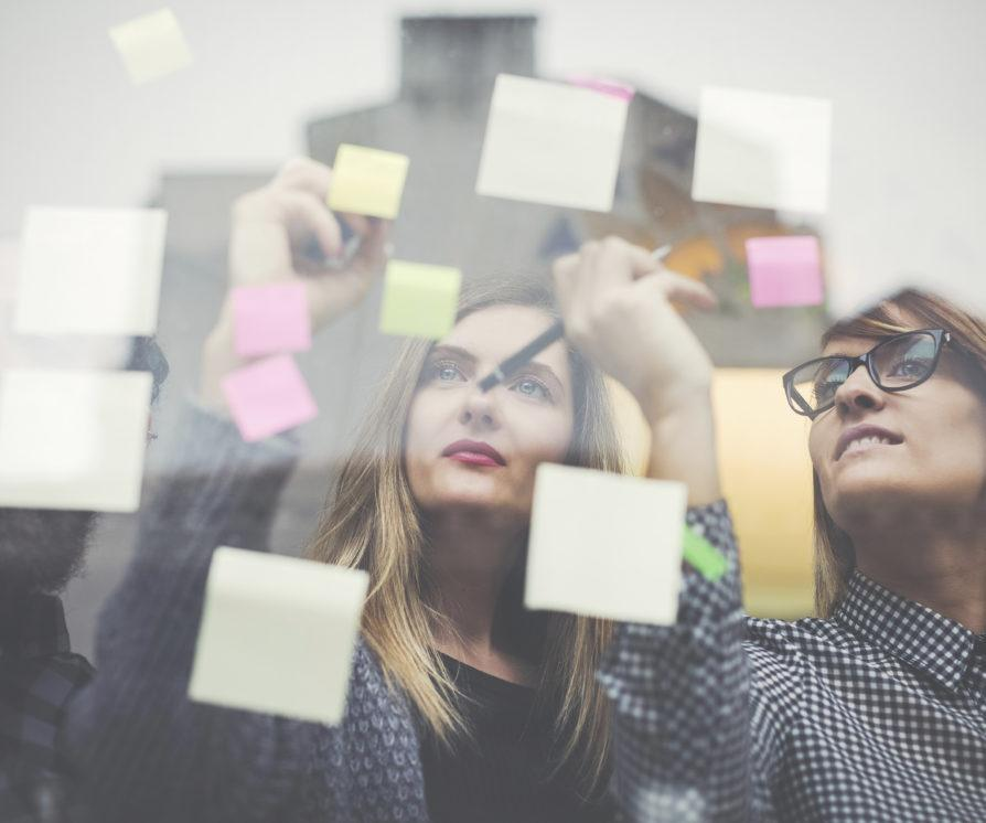 Two women looking at post it notes