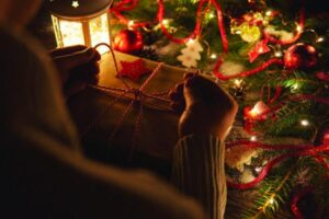Crop shot of person tying up colorful twine on wrapped Christmas present at table with glowing garland