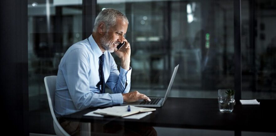 Shot of a mature businessman using his laptop and phone at work