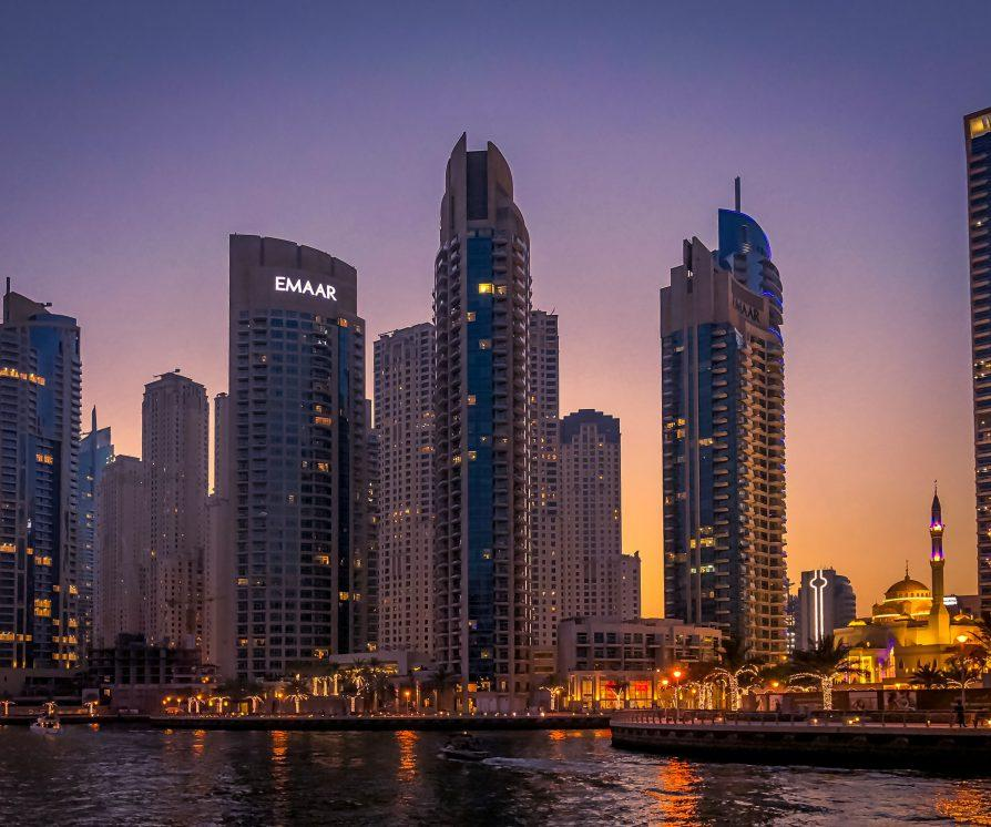 Dubai cityscape with sky scrapers and water in the foreground