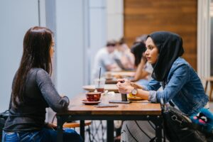 Two women talk over a table at a cafe