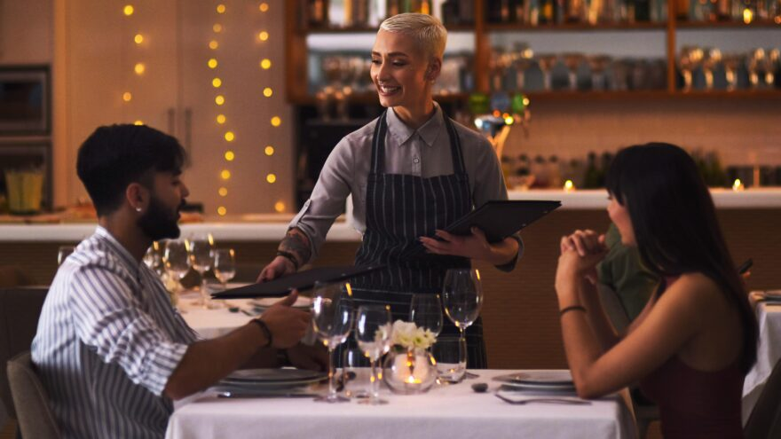 Shot of a waitress serving a couple in a restaurant