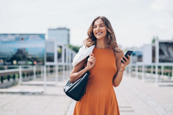 Young woman holding smart phone outdoors in the city
