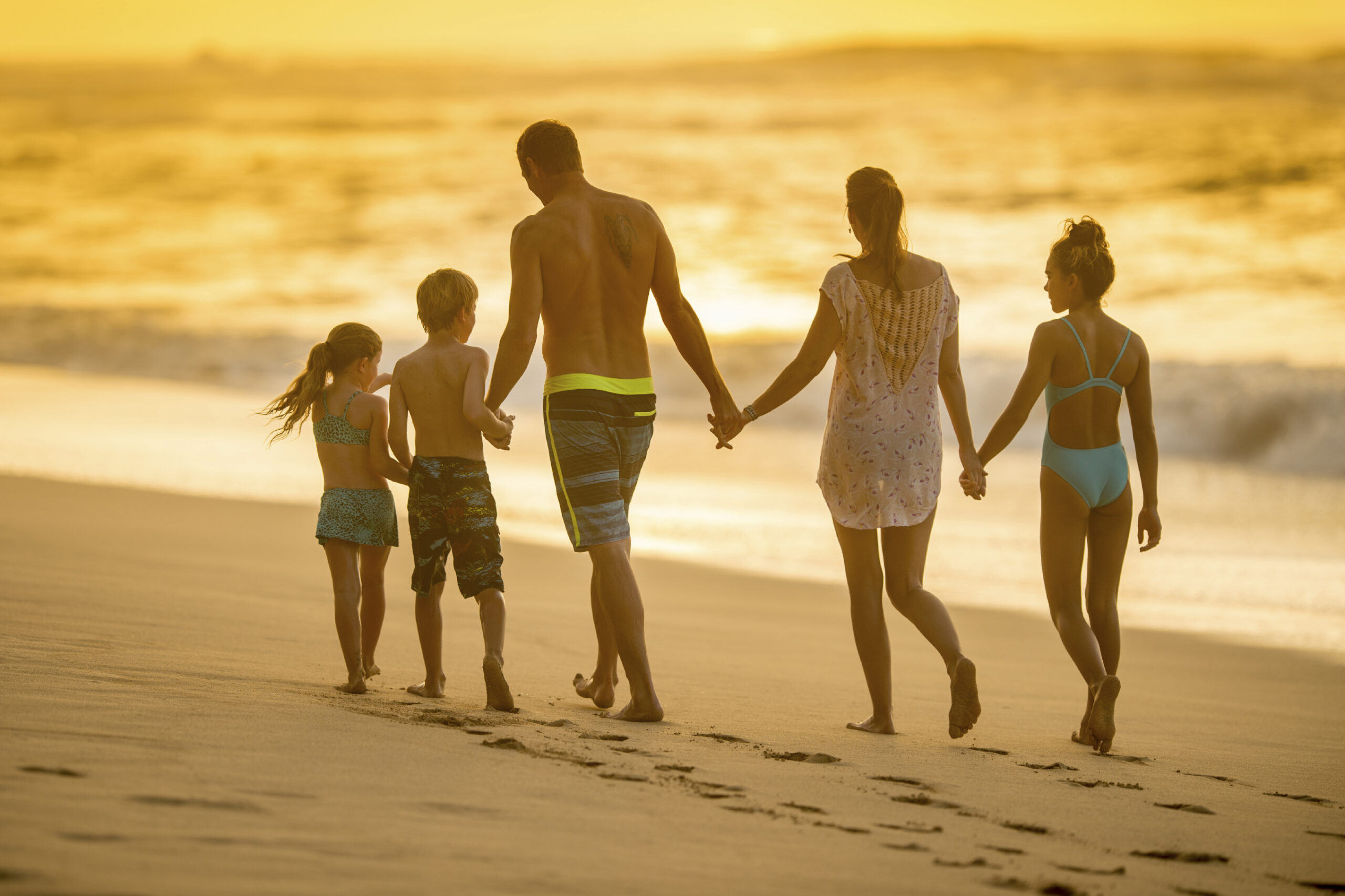 A family of five walking together down the beach