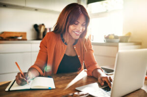 Woman sitting at the table working on her laptop smiling