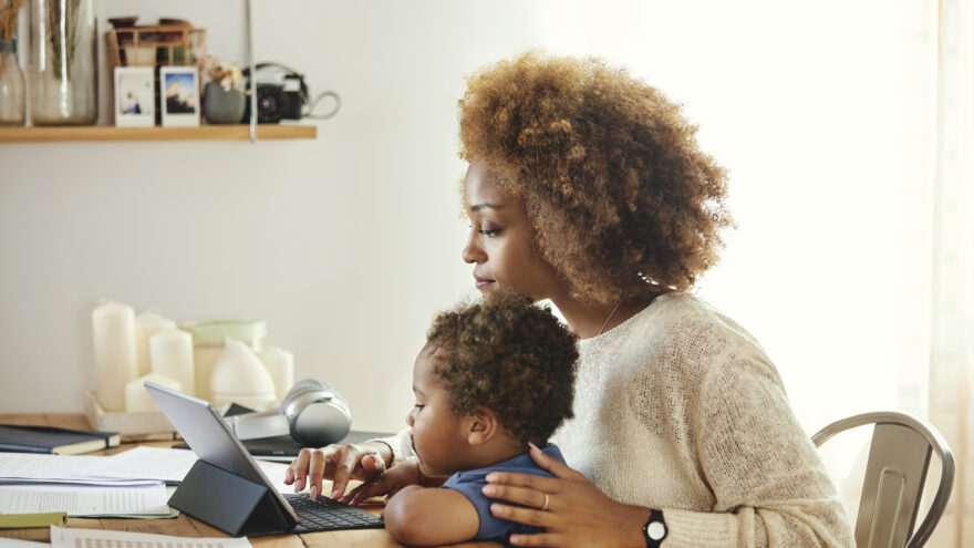 Mother with son working on digital tablet at home